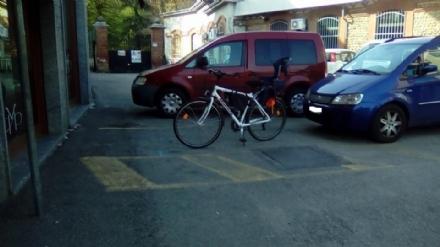 RIVALTA - Il parcheggio dei disabili è occupato da una bici e lauto che ci deve stare resta in mezzo alla strada