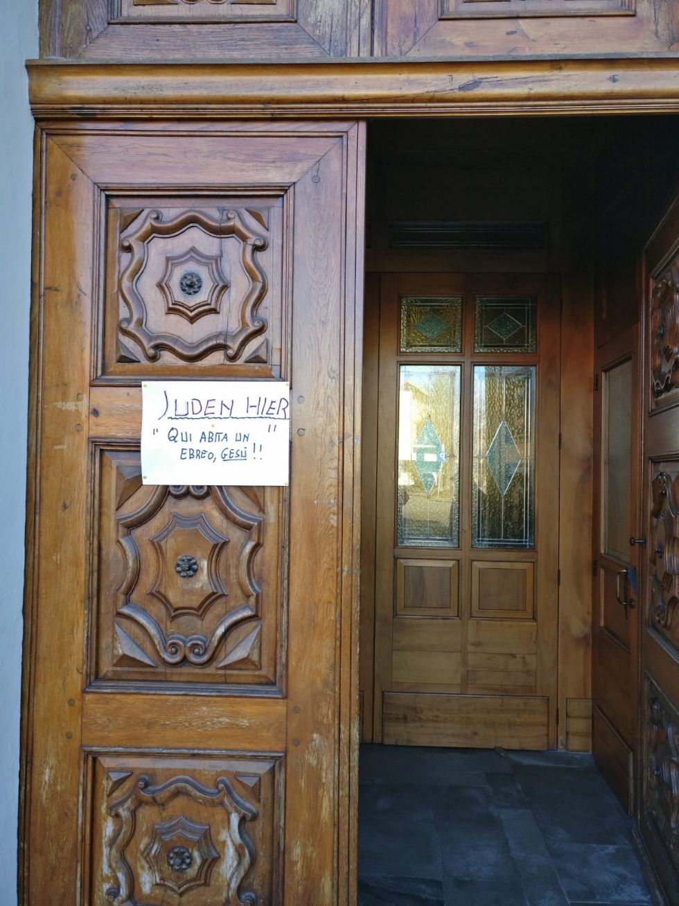 LA LOGGIA - Don Marini appende un cartello fuori dalla parrocchia: 'Juden Hier'